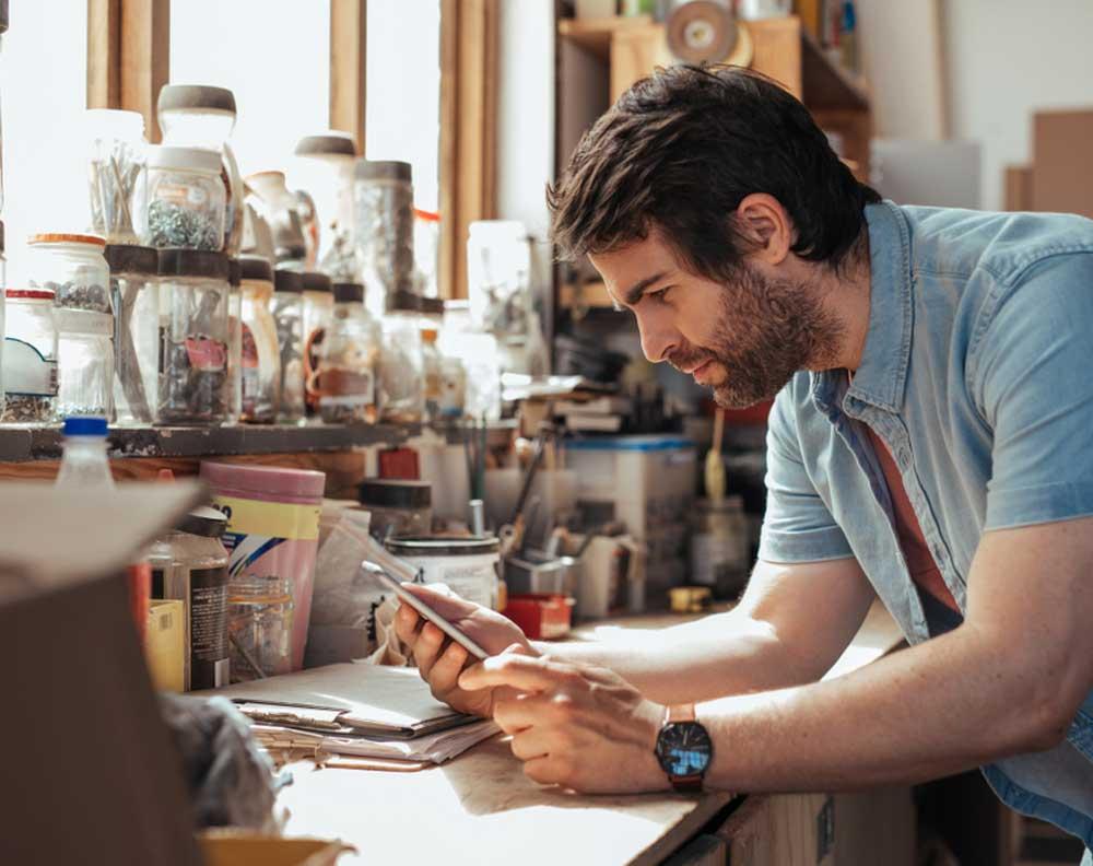 Hombre joven revisando en su negocio si le conviene utilizar tarjeta de crédito